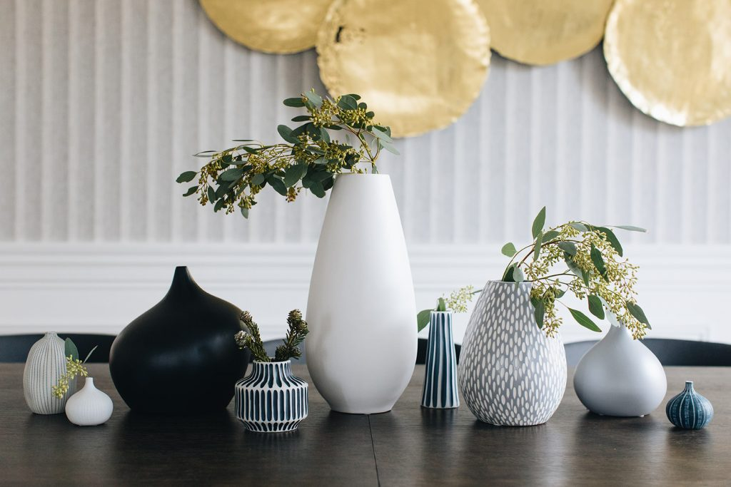 vases on dining table with greenery inside