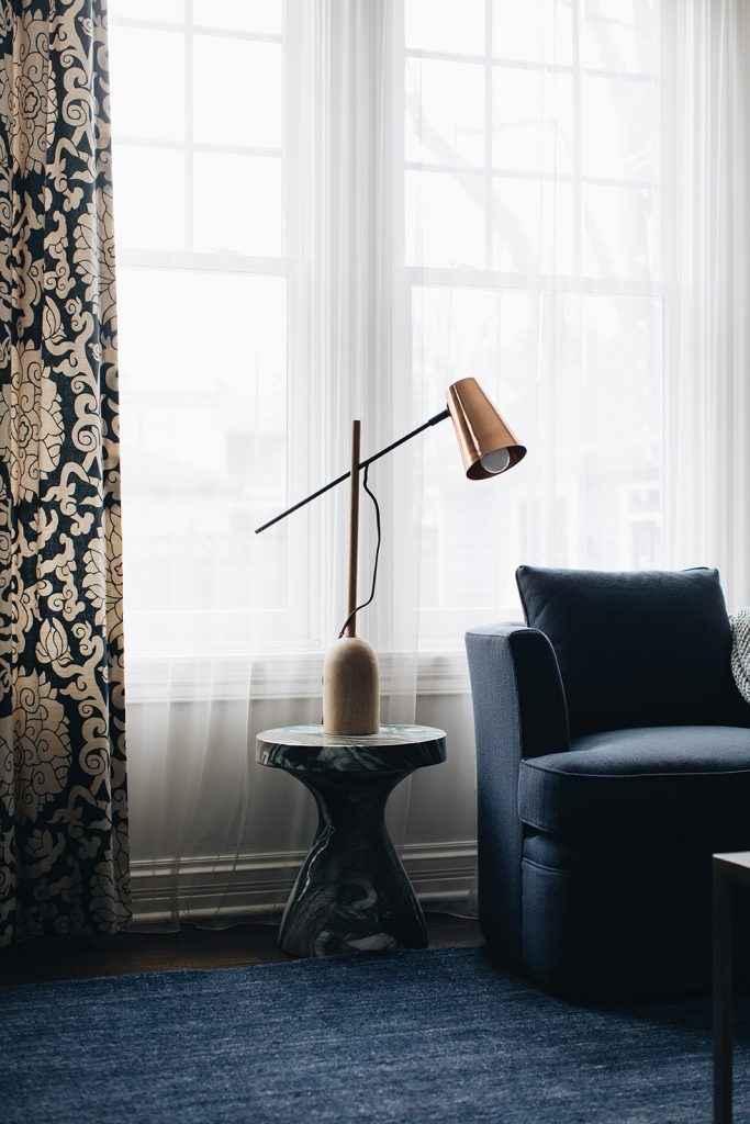 family room window with lamp and patterned drapery