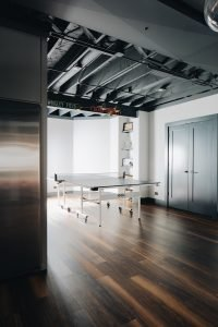 basement ping pong table area with exposed ceiling